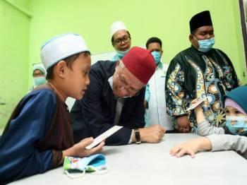 Dr Zulkifli Mohamad Al Bakri mendengar bacaan Al- Fatihah yang dibaca oleh adik Muhamad Aiman Haiqal Reza Asmar, 8, (kiri) sewaktu melawat kelas hafazan Al-Quran selepas menyampaikan bantuan Musa'adah COVID-19 di Anjung Pendidikan Asnaf hari ini. - Foto Bernama