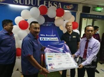 Ruslin (dua dari kiri) sewaktu Majlis Pelancaran Kemudahan ePayment dan Penyerahan Dokumen Pengenalan Diri di Ibu Pejabat JPN Terengganu di Wisma Persekutuan, di sini hari ini.