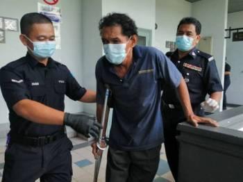 Kui Khiong (tengah) yang menggunakan tongkat keluar dari Mahkamah Majistret hari ini.