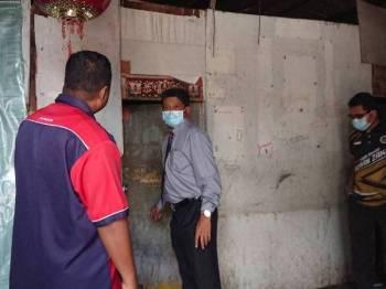 Zainal (kanan) melihat sebuah bilik sewa yang telah dikosongkan di Kampung Jawa, Melaka hari ini sebelum kerja-kerja merobohkan penempatan kayu itu dilakukan esok.