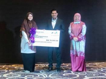 Hamdan (tengah) menyampaikan replika cek saguhati pesara berjumlah RM78,000 kepada wakil pesara pada Majlis Persaraan Warga Kerja MPK di sebuah hotel di Kuantan hari ini.