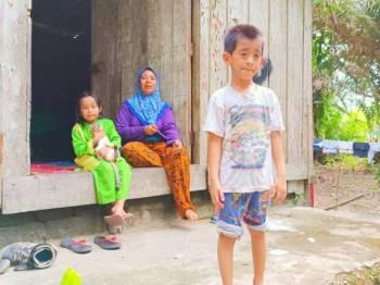 Wan Sharifah bersama anak perempuannya dan Mohd Shariman (hadapan) yang mengalami masalah pundi kencing atau nephrotic syndrome dan penyakit buah pinggang di rumah sewanya di Kampung Permatang Gading, Bukit Abal, Pasir Puteh.