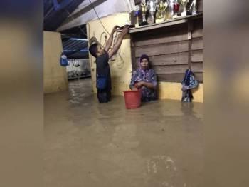 Penduduk memindahkan barang-barang berharga ke tempat tinggi selepas rumah mereka dinaiki banjir kilat di Kampung Perik, Kuala Nerang, semalam. - Foto Ihsan penduduk