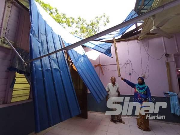 Rahimah dan suaminya menunjukan keadaan kediamannya yang rosak akibat kejadian itu.