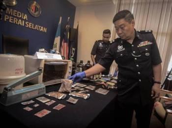 Chong Chern menunjukkan pelbagai jenis dadah yang dirampas dari pasangan terbabit.