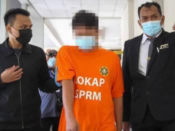 Pemilik syarikat pembekalan pasir (tengah) dibawa pegawai SPRM ke Mahkamah Khas Reman Seremban hari ini.