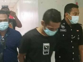 Mohd Anuar (tengah) dibawa keluar dari Mahkamah Sesyen Kuala Terengganu hari ini selepas dijatuhi hukuman lima tahun penjara, dua sebatan serta dua tahun pengawasan polis.