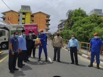 Fadhil (tiga dari kiri) menyerahkan ayam segar kepada petugas untuk diagihkan kepada penduduk Flat Tongkang Yard, Seberang Perak hari ini.