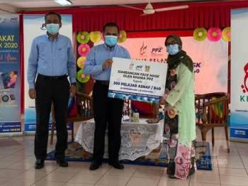Ahmad Shukri (dua dari kanan) menyerahkan replika sumbangan kepada Guru Besar SK Wangsa Maju Seksyen 10, Saadiah Mohd Noh pada Majlis Pelancaran Serahan Sumbangan Pelitup Muka Khaira PPZ di SK Wangsa Maju Seksyen 10 di Kuala Lumpur semalam.