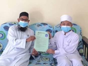 Mohd Sharif (kiri) bersama Mohd Haikal menunjukkan borang kemasukan ke pusat tahfiz berkenaan.