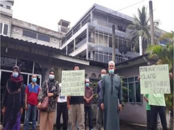 Abdullah (dua kanan) bersama sebahagian penduduk Kampung Bohor, Mukim Hutan Kampung membuat bantahan terhadap kilang tersebut yang berdekatan dengan kediaman mereka.