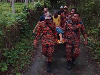 Pasukan penyelamat mengusung Hassan keluar dari lokasi warga emas itu hilang di Kampung Bukit Batu, Kuala Krai hari ini.