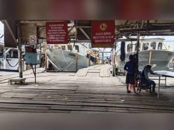 Kapal nelayan tersadai di salah satu jeti di sekitar Pekan Kudat selepas operasi pusat pengumpulan ikan ditutup sejak Selasa lalu susulan Kluster Basung di Kudat.