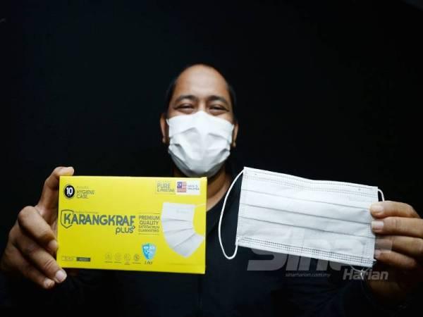Pengurus Besar Pemasaran Karangkraf Medicare, Raja Shahfaizal Khairudin menunjukkan pelitup muka yang dihasilkan Karangkraf Medicare. -Foto:ROSLI TALIB