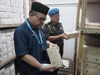 Md Arifin melakukan pemeriksaan terhadap aiskrim dan plastik aiskrim yang mempunyai logo halal di sebuah kilang di Kampung Parit Marjunit, Benut, Pontian semalam.