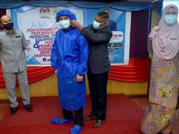 Burhanuddin (kiri) melihat Hanafiah memakaikan pakaian PPE yang berjaya disiapkan.  - Foto: UPDI