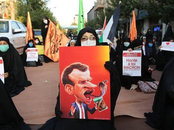 Seorang wanita membawa plakad tertera karikatur Macron berlidah bercabang seperti ular ketika protes di luar Kedutaan Perancis di Teheran, Iran.