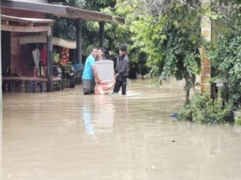 Penduduk di Kampung Petaling, Kuala Nerus memindahkan barangan selepas kediaman mereka dinaiki air.