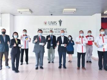 Taufiq (empat dari kiri) bersama kakitangan UMS dan SCCC menunjukkan kit ujian Covid-19 yang akan dikaji tahap ketepatan dan keberkesanannya.