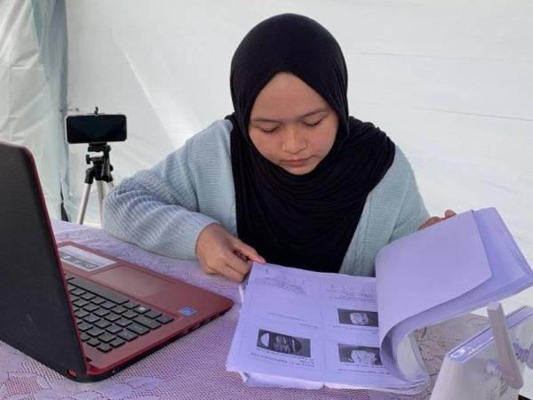 Nurlieda Khaleeda mengikuti kelas dalam talian, mengulang kaji pelajaran dan menjawab soalan peperiksaan di dalam khemah yang dibina bapanya.