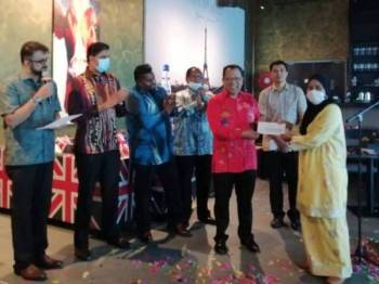 Zuhairi (tiga dari kiri) menyampaikan sumbangan untuk misi bantuan banjir kepada wakil NGO di Tanjung Lumpur, Kuantan hari ini.