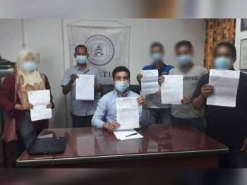 Mohamad Yusrizal (duduk) dan mangsa menunjukkan laporan polis dan Suruhanjaya Komunikasi dan Multimedia Malaysia (SKKM) di Pejabat Cake hari ini.