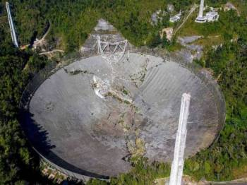 Teleskop Arecibo terjatuh ke dalam sebuah piring radio di Arecibo, Puerto Rico semalam. - Foto AFP