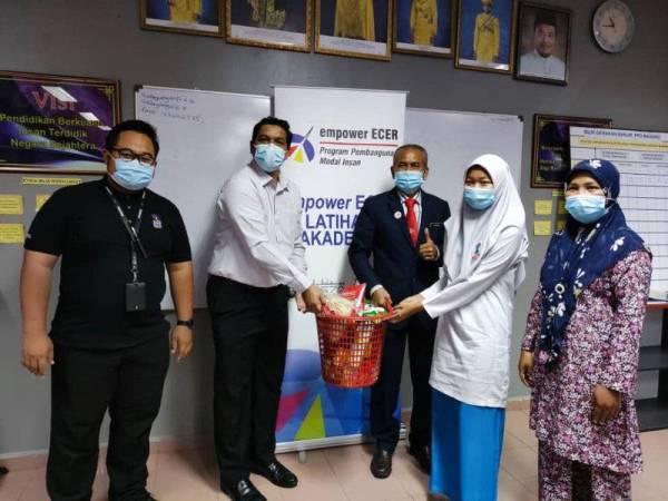 Mohd Nazron (dua dari kiri) menyampaikan sumbangan kepada salah seorang pelajar cemerlang.