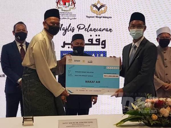 Pengerusi SPAN, Wan Hassan Mohd Ramli (depan, kiri) menyerahkan sumbangan wakaf berjumlah RM2 juta kepada Amir pada Majlis Pelancaran Wakaf Air.
