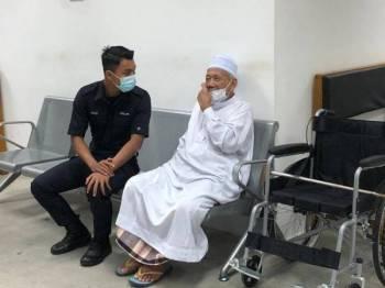 Tertuduh, Lokman Ahmad, 83, (kanan) dikawal polis keluar dari Mahkamah Majistret selepas denda diputuskan terhadapnya atas dua kesalahan yang dilakukan.