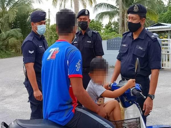 Mohd Azmir (kanan) menyoal siasat seorang bapa bersama anaknya yang gagal mematuhi SOP dalam tempoh perlaksanaan PKP.