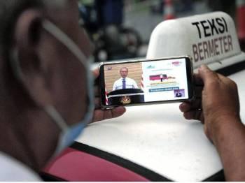 Pemandu teksi, Sahar Mustafa, 58, mengambil kesempatan mendengar Perutusan Perdana Menteri melalui telefon pintar sambil menunggu penumpang ketika tinjauan di Seksyen 14 Shah Alam hari ini. - Foto Bernama