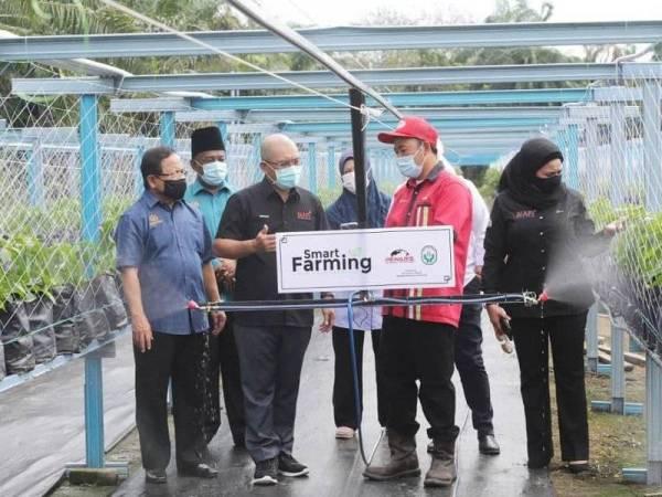 Ronald (dua dari kiri) dan Timbalan Menteri MAFI 1, Datuk Seri Ahmad Hamzah (kiri) mendengar taklimat mengenai 'smart farming' ketika melawat PPHP PPK Kuala Langat pada Selasa.