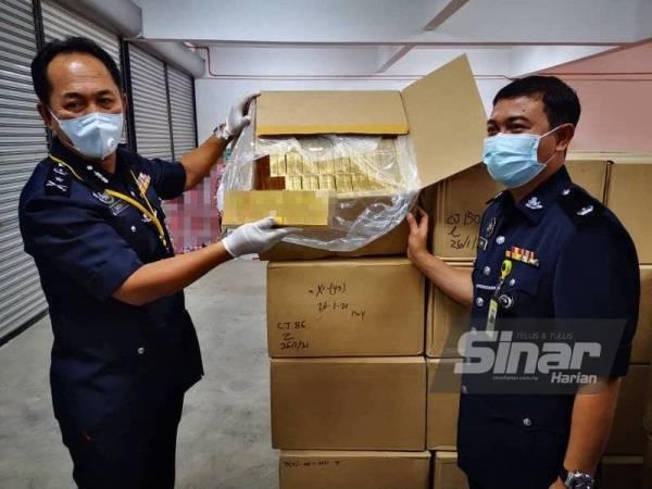 Jauteh (kiri) menunjukkan rokok yang dirampas polis di kawasan lapang berhampiran Taman Famosa, Jalan Bundusan, Penampang.