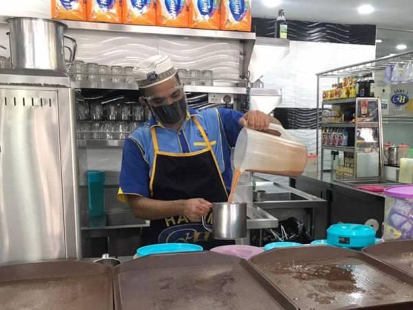 Pekerja Restoran Hakim, Shah Alam bekerja dengan pematuhan SOP pada Khamis.