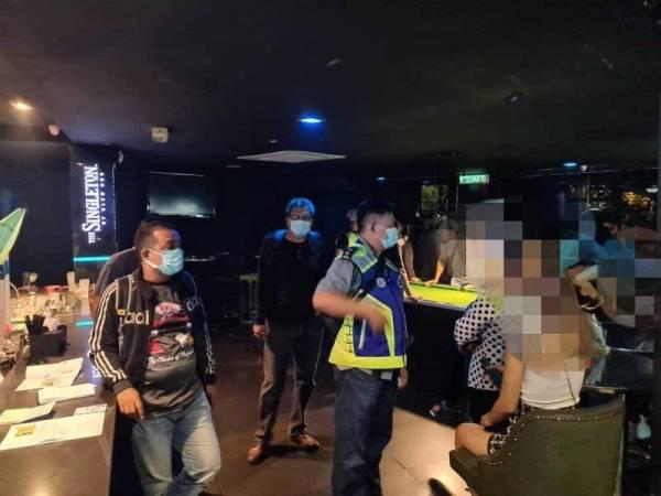 Polis memeriksa beberapa pelanggan dalam serbuan yang dijalankan di dua pusat hiburan di Kuala Lumpur pada Khamis.