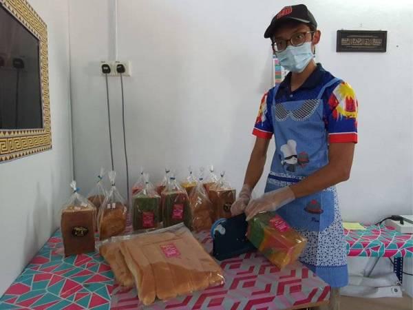 Mohd Faez Hafizie sedang membungkus roti ban yang dihasilkan