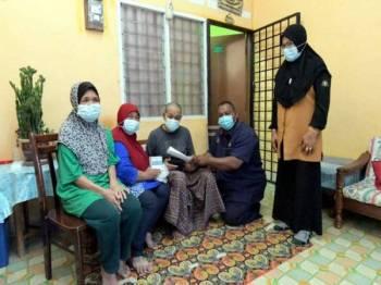 Warga emas yang menjaga suaminya yang buta, Fauziah Ali, 64 (dua, kiri) menerima kunjungan dan sumbangan daripada Pengerusi Biro Kebajikan, Jawatankuasa Penyelaras Khas Dewan Undangan Negeri (JPKD) Penggaram, Mohd Hamidi Mad Tap (dua, kanan) di kediamannya, di Taman Bukit Perdana. Fauziah juga terpaksa membawa suaminya itu, Mahat Juraimi, 66 (tengah) dengan menunggang motosikal ke klinik yang jauhnya kira-kira tujuh kilometer setiap bulan untuk rawatan dan mengambil ubat, walaupun dia sendiri tidak mempunyai lesen.- Foto Bernama