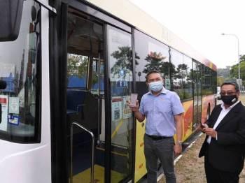 Ng Sze Han (kiri) menunjukkan penggunaan Scan To Ride menerusi Aplikasi Citizen E-Payment (CEPat) selepas melancarkan Scan To Ride Perkhidmatan Bas Smart Selangor, hari ini. Bersamanya ialah Datuk Bandar Shah Alam, Datuk Haris Kasim. - Foto Bernama
