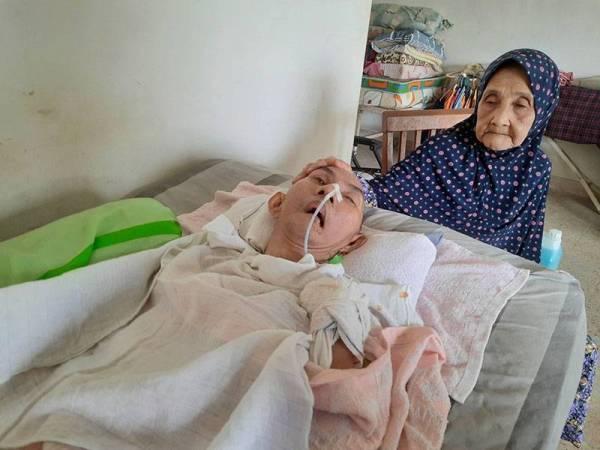 Zainun (kanan) menjaga Azman yang terlantar di katil selama 21 tahun ketika ditemui di rumah di Lorong Kubang Buaya, Kuantan pada Sabtu.