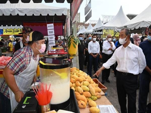 Perdana Menteri Tan Sri Muhyiddin Yassin mengadakan tinjauan ke Bazar Ramadan Presint 3 pada Rabu.  Foto Bernama