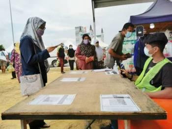 Pengunjung membuat imbasan suhu badan, kod QR melalui aplikasi MySejahtera dan menulis buku rekod kehadiran sebelum memasuki bazar Ramadan di dataran Jambatan Angkat, Kuala Terengganu pada Rabu.