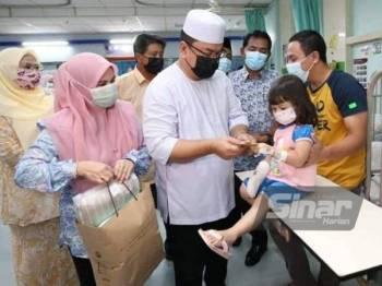 Sulaiman dan isteri, Datin Munira M Yusop (kiri) menyantuni pesakit cilik sempena Program Santuni Kasih Permata Hati sempena Sambutan Ulang Tahun Ke-18 Majlis Bandaraya Melaka Bersejarah (MBMB) di Hospital Melaka pada Khamis.
