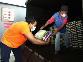 Pekerja Jakel menyusun beras ketika tinjauan di Masjid Jamek Kampung Baru hari ini. Pihak Jakel akan menyumbangkan sebanyak 300 bungkusan, mengandungi gula, minyak, tepung dan sardin bagi setiap satu bungkusan serta 600 kampit beras kepada golongan asnaf. - Foto Bernama