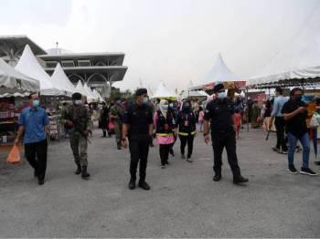 Anggota PDRM dan ATM membuat rondaan bagi meninjau SOP dipatuhi para pengunjung semasa membeli juadah berbuka puasa ketika tinjauan Bernama di Tapak Bazar Ramadan Presint 3 Putrajaya hari ini. - Foto Bernama