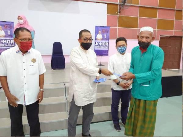 Khaled Nordin (dua dari kiri) menyampaikan bantuan kepada penerima pada Majlis Penyerahan Insentif Johor Berkebajikan E-Kasih 2021 di Dewan Serbaguna Taman Cendana, Pasir Gudang pada Jumaat.