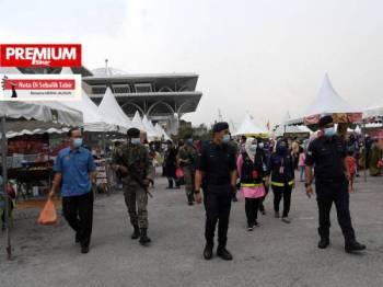 Anggota PDRM dan ATM membuat rondaan bagi meninjau SOP dipatuhi para pengunjung semasa membeli juadah berbuka puasa di Tapak Bazar Ramadan Presint 3 Putrajaya hari ini. - Foto Bernama