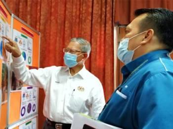 Mustapa (kiri) ketika mengadakan lawatan kerja rasmi ke Jabatan Perangkaan Malaysia Kelantan di Wisma Persekutuan, Kota Bharu pada Ahad.