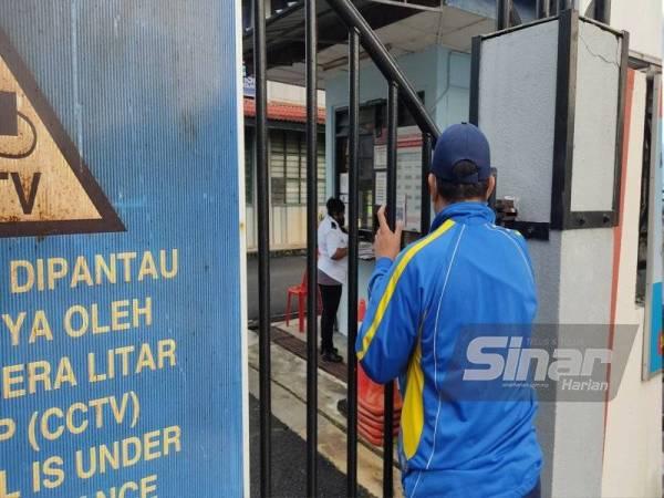 Seorang lelaki dipercayai salah seorang ayah kepada pelajar di Sekolah Menengah Kebangsaan Puchong Utama (1) hadir ke sekolah untuk mengambil buku latihan anaknya di pintu pagar.