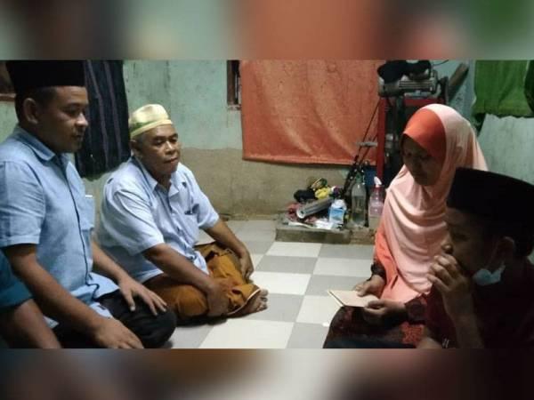 Jasnizam (kiri) hadir menyampaikan sumbangan kepada Sakiroh di di Perumahan KEDA Kampung Semeliang, Kuala Nerang pada Isnin.